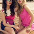 Two beautiful glamour women in bright clothes posing on beach — Stock Photo #48691471