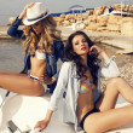 Two sexy beautiful girls in bikini relaxing on beach — Stock Photo #48691935