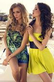 Two beautiful glamour women in colorful dresses on beach — Stock Photo