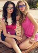 Two beautiful glamour women in bright clothes posing on beach — Stock Photo