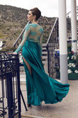 Fashion photo of beautiful glamour model with elegant hairstyle in luxurious silk blue dress posing at dock — Stock Photo