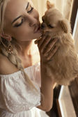 Beautiful sexy woman kissing small cute dog — Stock Photo