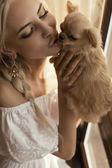 Beautiful sexy woman kissing small cute dog — Stock Photo