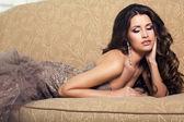 Sexy beautiful woman in luxurious dress lying on divan — Stock Photo