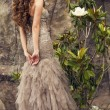 Beautiful woman with long curly hair in luxurious dress — Stock Photo