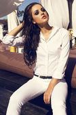 Sexy girl with dark hair in white shirt and pants posing on beach — Stock Photo