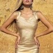 Sexy girl with long blond hair in gold dress posing on beach — Stock Photo #50223057