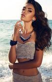 Beautiful girl with dark hair in elegant dress with bijou — Stock Photo