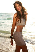 Beautiful girl with dark hair in fashion dress posing on beach — Stock Photo