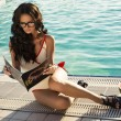 Sexy girl with dark hair reading magazine beside a swimming pool — Stock Photo #51388253