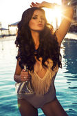 Sexy girl with dark hair in fashion swimsuit posing in swimming pool — Stock Photo