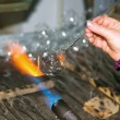 Glassblower heats the glass piece for shaping the future Christmas ornament — Stock Photo #36393995