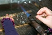 Glassblower heats the glass piece — Stock Photo