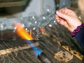 Glassblower heats the glass piece for shaping the future Christmas ornament — Stock Photo
