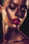 Beautyful girl with gold glitter on her face — Stock Photo