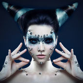 Demon girl with spikes on the face and body — Stock Photo