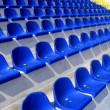 Empty blue and yellow plastic armchairs on a stadium tribune — Stock Photo