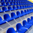 Empty blue and yellow plastic armchairs on a stadium tribune — Zdjęcie stockowe