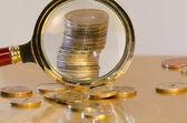 Ein stapel von münzen unter der lupe — Stockfoto