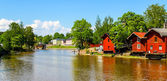 Old red warehouses alongside river Porvoo — Stock Photo