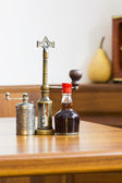 Still life composition with metallic pepper grinder and small bottle of aromatic vinegar — Stock Photo