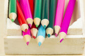 Colored pencils in a wooden box — Stock Photo
