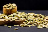 Kitchen cutting board and pumpkin unshelled seeds — Stock Photo