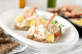 Appetizer of shrimp, pineapple, garlic and melted cheese — Stock Photo