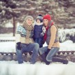 Happy young family portrait on winter surrounded by snow. — Stock Photo