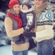 Happy young family portrait on winter surrounded by snow. — Stock Photo #36874973