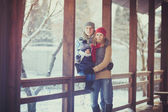 Happy young family portrait on winter surrounded by snow. — Photo