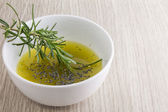Rosemary olive oil sauce in bowl on wood background — Stock Photo