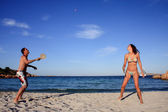 Young couple playing tennis on a beach. — Stockfoto