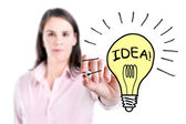 Young business woman drawing a light bulb. — Stock Photo
