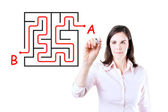 Young businesswoman finding the maze solution writing on the whiteboard. Isolated on white. — Stock Photo