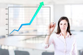 Young business woman writing over achievement graph. Office background. — Stock Photo