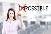 Businesswoman choosing Possible instead of Impossible. Office background. — Stock Photo