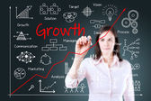 Young business woman writing growth graph. Blue background. — Stock Photo