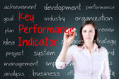 Young business woman writing key performance indicator (kpi) concept. Blue background. — Stock Photo
