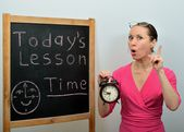 Woman teacher in school tells a subject about time — Stockfoto