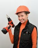 Woman smiling with working tool shurupovert in hand — Stock Photo