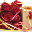 Golden gift box and a bouquet of red roses in a still life — Stock Photo