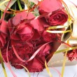 Golden gift box and a bouquet of red roses — Stock Photo