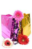 Colorful gift bags, bead and flowers for the holiday still life — Stock Photo