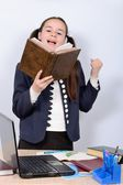 Teen schoolgirl in the classroom reading a book emotionally — Stock Photo