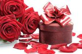 Gift box, petals and a bouquet of red roses — Stockfoto