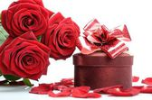 Gift box, petals and a bouquet of red roses — Stock Photo