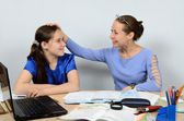 Gracious teacher praises and pats on the head with a good pupil girl — Stock Photo