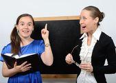 Pedagogo mujer y una niña cerca de pizarra estudiando con un libro — Foto de Stock
