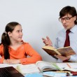 Teen schoolgirl listens attentively as the teacher reads a book — Stock Photo #46817077